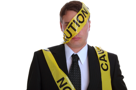 Man dressed in a business suit with caution tape wrapped around him.  Studio isolated on white.